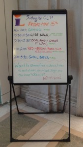 An easel whiteboard with CLP events written on it in different colors