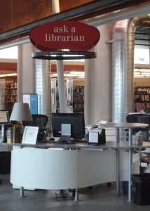 "An ""ask a librarian"" sign hanging over a reference desk at the Squirrel Hill branch library"