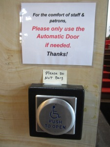 Laminated sign over post-it over button to open door mechanically