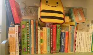 Shelf of board books with bee lunchbox on top