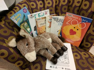 Storytime books on chair, with donkey puppet and coloring sheets