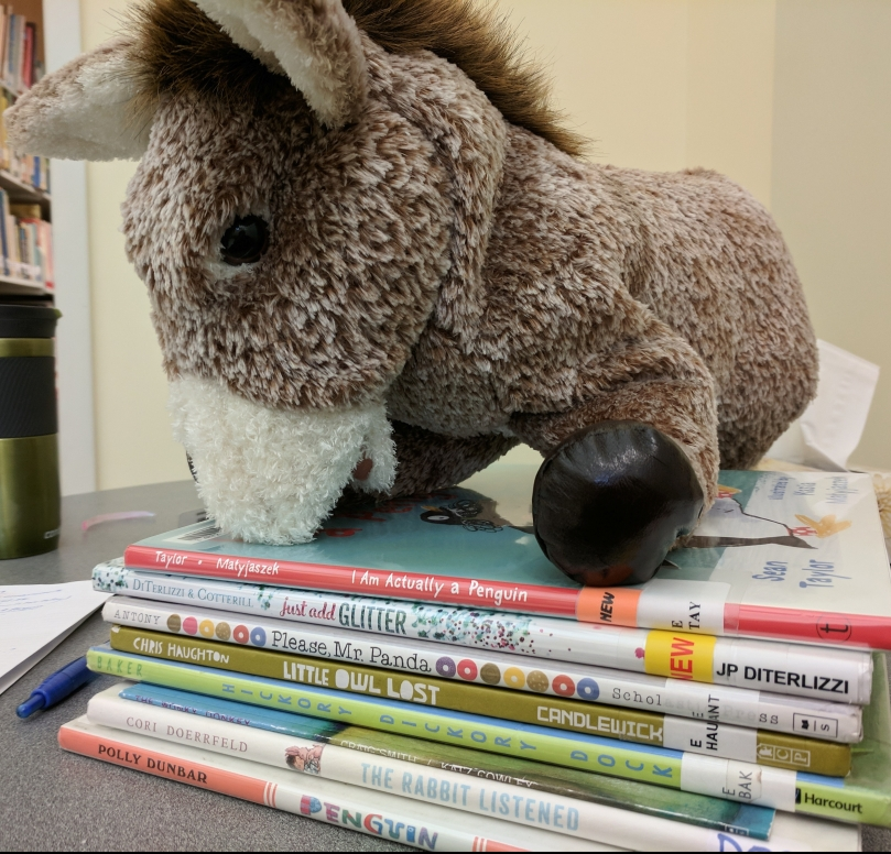 Donkey puppet atop stack of picture books