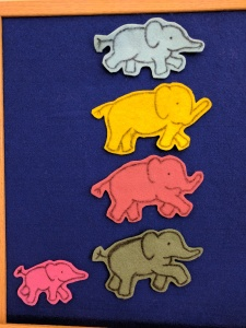 Blue, yellow, red, and green felt elephants on felt board