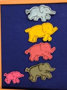Blue, yellow, red, and green felt elephants on felt board