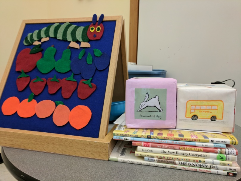 Flannel board with caterpillar and fruit, yoga cube, song cube, picture books