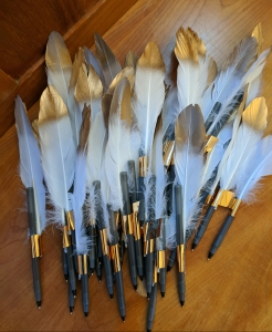 Gold-tipped feathers attached to pens