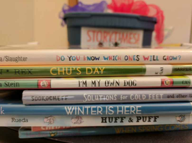 Stack of storytime books, with storytime box and scarves in the background