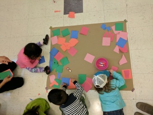 Bird's-eye view of kids gluing squares to paper
