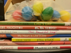 Stack of picture books with bag of shaker eggs on top