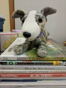 Greyhound stuffed animal on stack of picture books