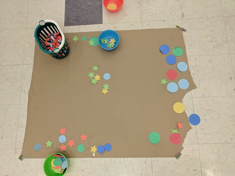Craft: gluing colored paper shapes to butcher paper